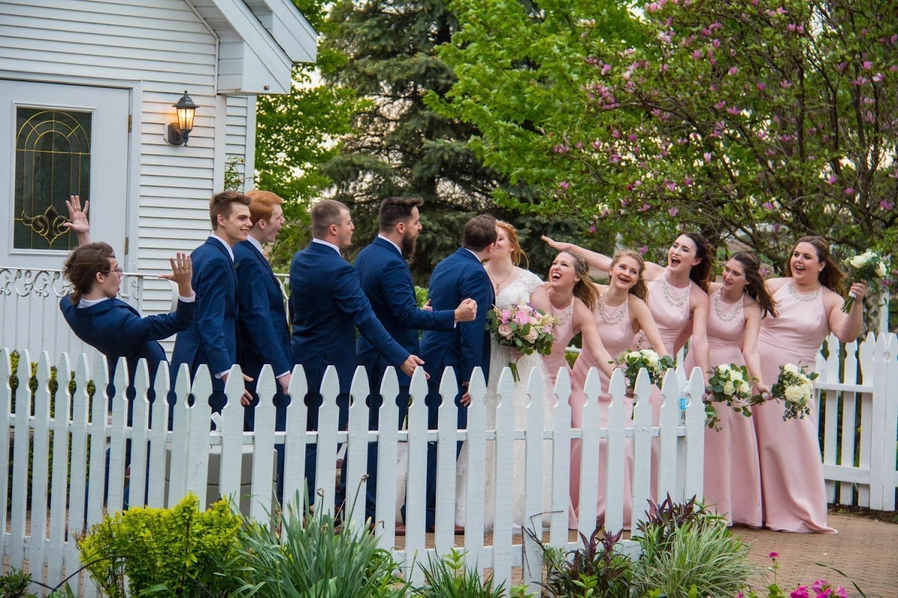 Bridal party posing for wedding photos in front of our wedding chapel and white picket fence. Instagram Gallery