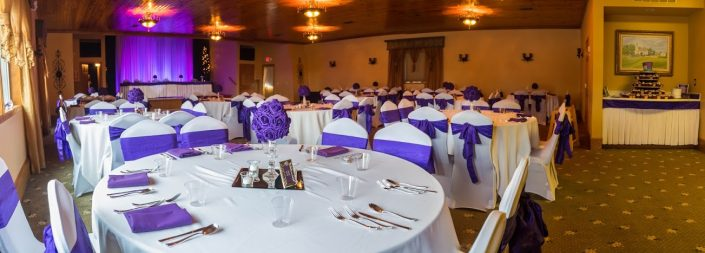Purple decorated wedding reception hall with purple sashes lights & flowers.
