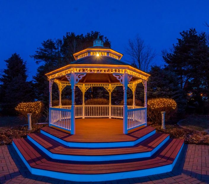 Glowing garden gazebo with a clear blue sky.
