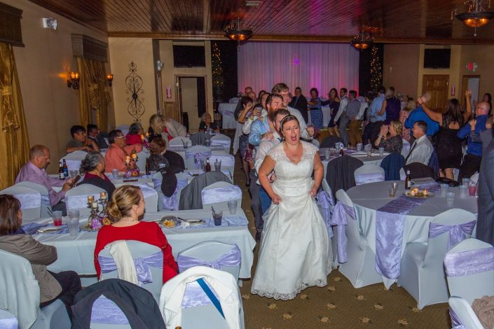 Bride leading a conga line through the reception hall and dance floor.