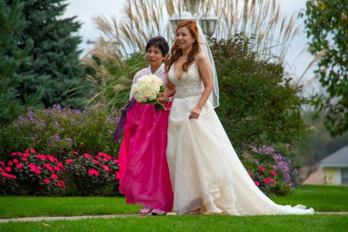 Bride and mother walking through our gardens from the chapel to our gazebo.