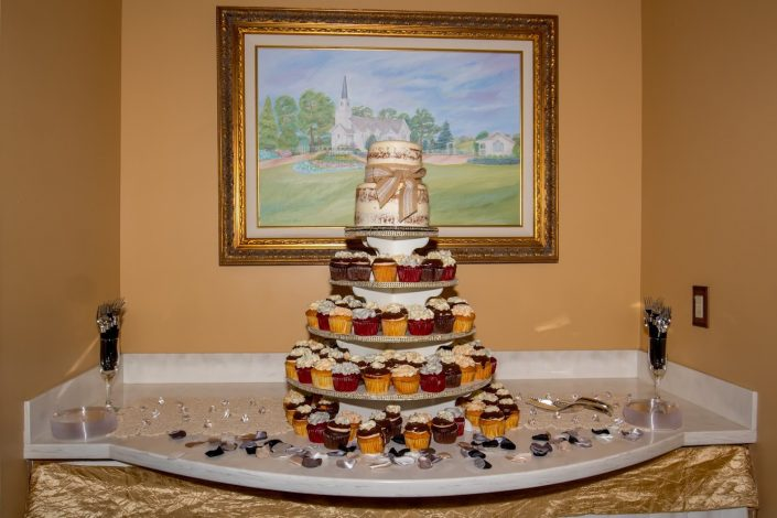 cake table filled with cupcakes and topped with a wedding cake with our chapel paining in the background