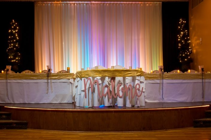 Empty head table with rainbow curtain waiting for the reception to start.