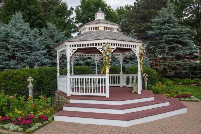 Garden gazebo covered in floral arrangements for a wedding.