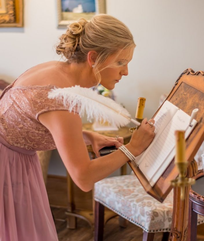 Bridesmaid signing our guest book with a feather pen