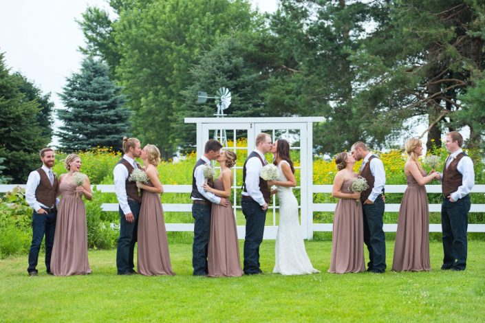 brid groom and most of the bridal party kissing in front of field door fence
