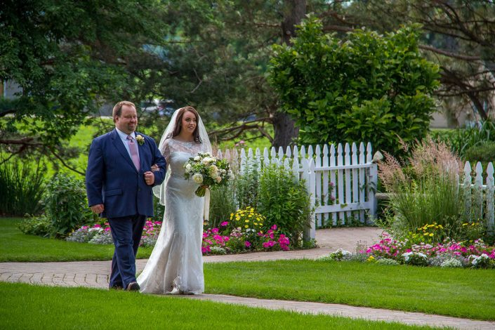 bride and father walking down our path through our gardens past our flowers and picket fence