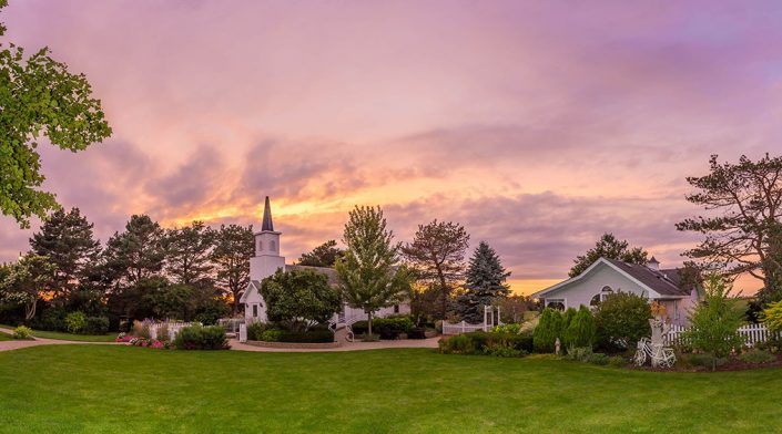 panorama of purple skies over chapel in the pines wedding & Banquet hall and gardens