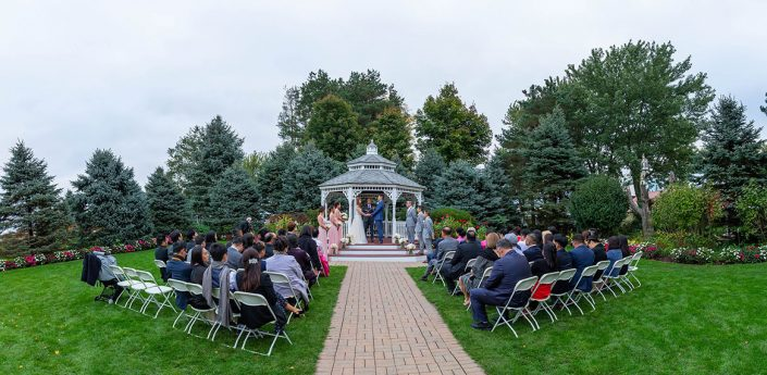 View of the gazebo, trees and gardens during a wedding ceremony