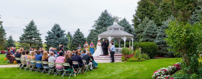 View of the gazebo, trees flowers, and gardens during a wedding ceremony