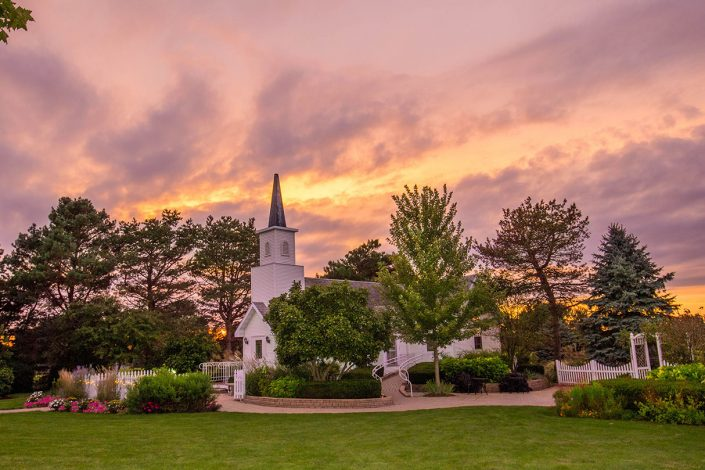Purple and orange skies over chapel in the pines