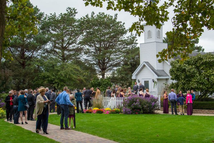Guests gather round the chapel after the wedding ceremony for a group picture. Reception & Wedding Grounds Videos