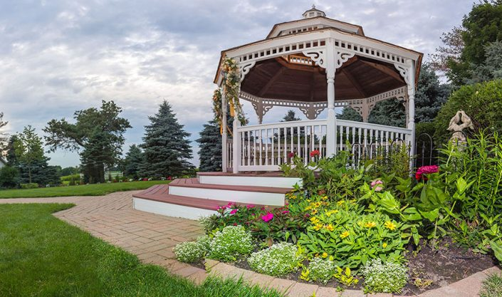View on a cloudy day of our garden gazebo withcolorful flowers