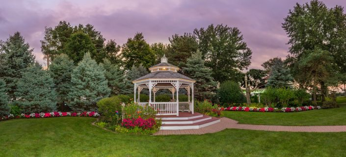 view of our flowers, trees, gardens and gazebo during a purple skied dusk