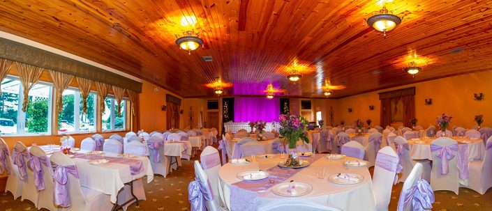 view of a purple decorated and lit wedding reception in our banquet hall