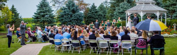 Panorama of a full sized wedding ceremony at our garden gazebo