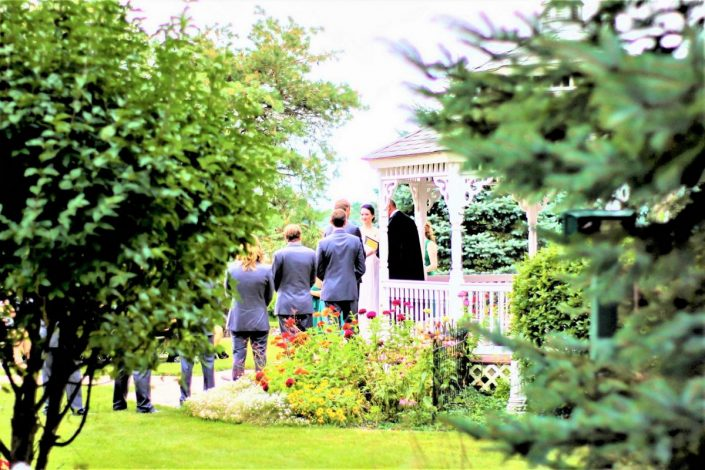 view through the pines and gardens of a wedding ceremony at our gazebo