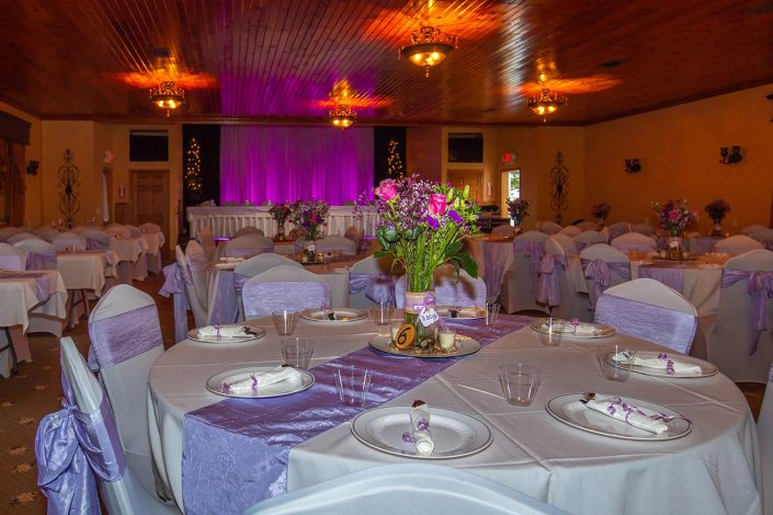 beautifuly decorated reception hall with flowers, lights and purple sashes