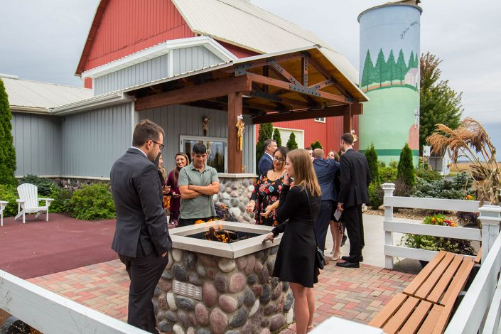 wedding guests gathered around our new fire pit outside our wedding reception hall, barn, and silo