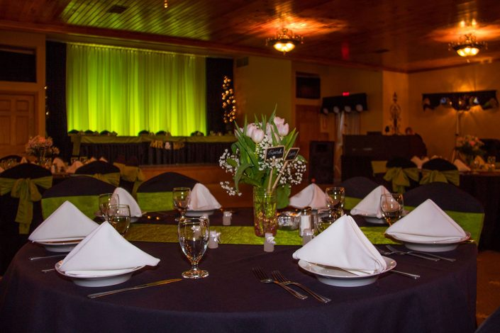 tables set with napkins, flowers, green sashes, and lights in our wedding reception banquet hall