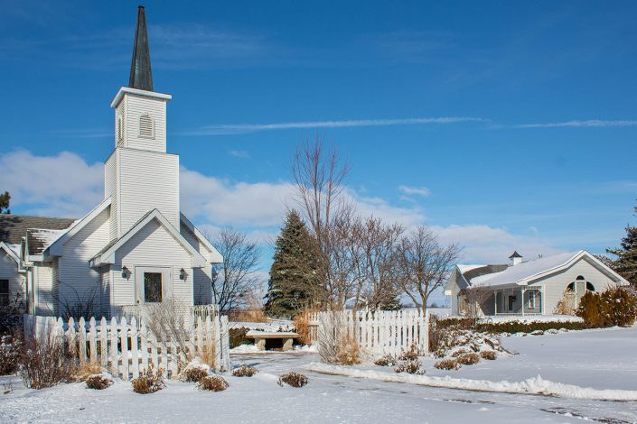 winter at chapel in the pines with snow covered gardens, chapel, and bridal cottage