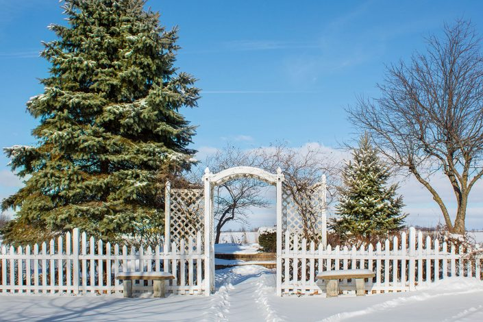 winter at chapel in the pines with snow covered fence, trellis and gardens