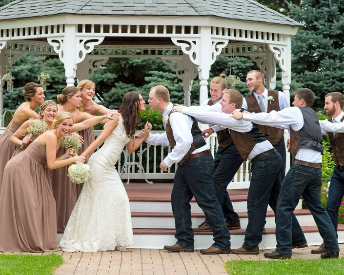 bridal party comically trying to keep the newly married couple from kissing in front of our wedding gazebo