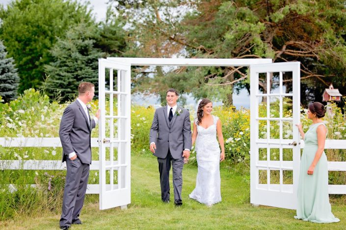 bride and groom walking through the fence doorway from our field of flowers